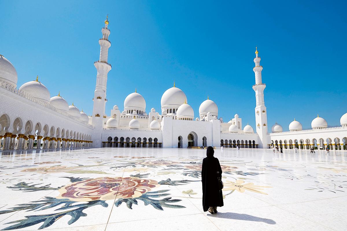 Woman wearing an abaya in the mosque courtyard. United Arab Emirates, UAE, Abu Dhabi, Sheikh Zayed Grand Mosque.