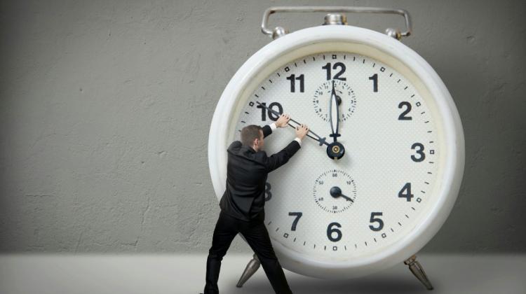 Na zdjęciu duży zegar, przed nim stoi mężczyzna. Mężczyzna trzyma wskazówki zegara.